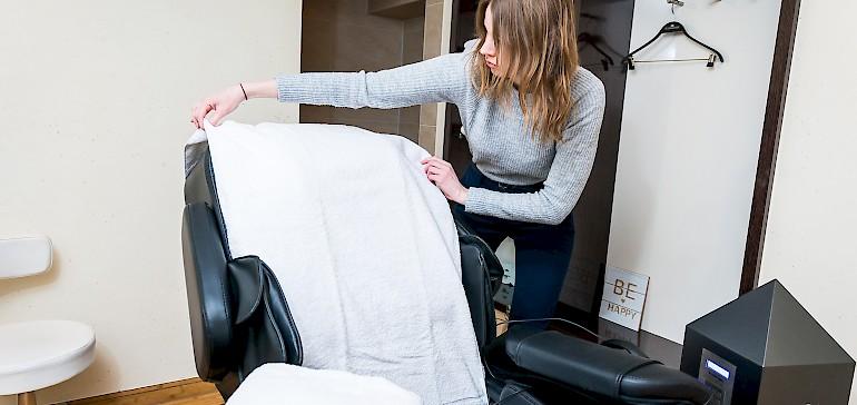 De stoel met de bereidgelegde handdoeken afdekken